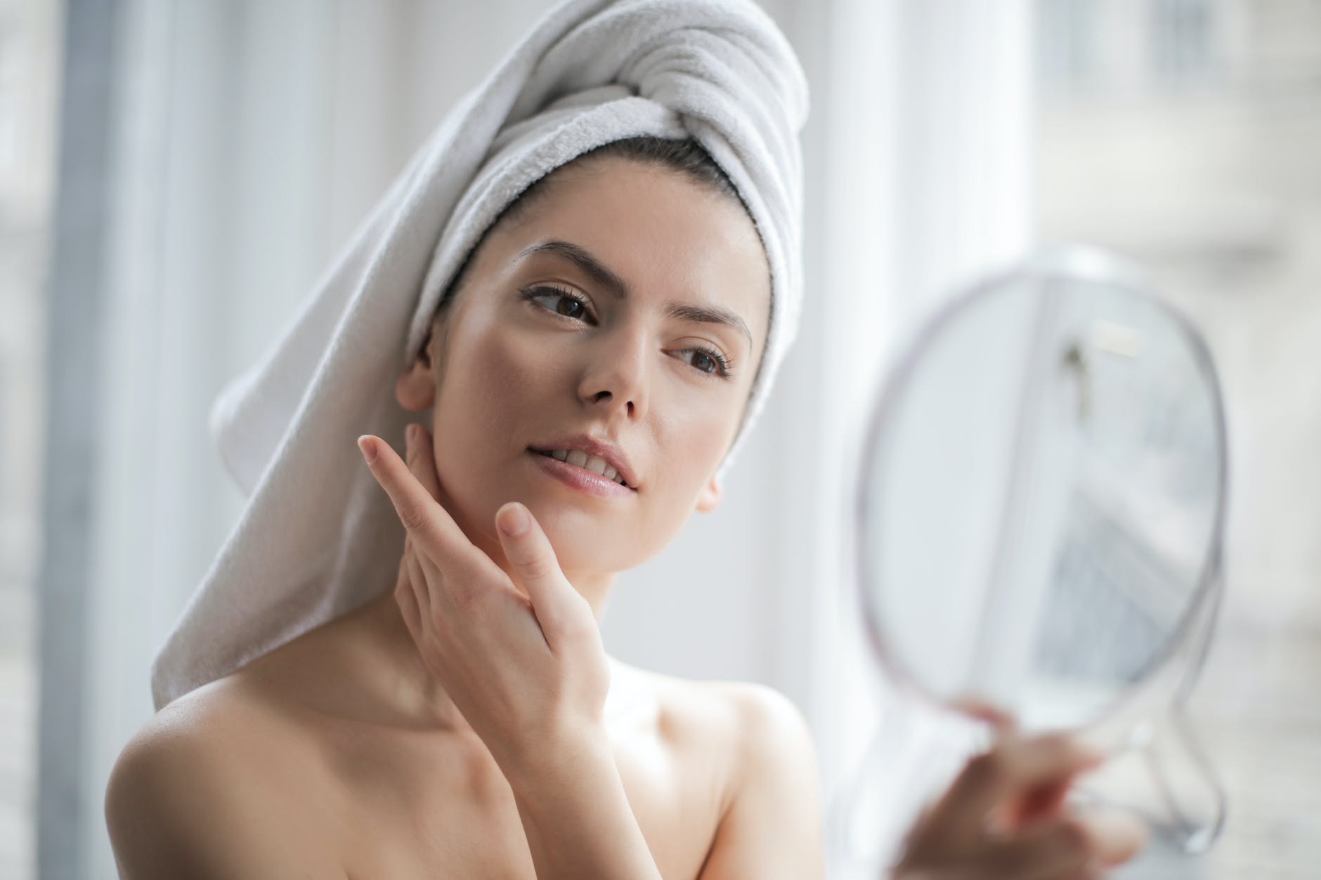 woman looking into a mirror with a towel drying her hair